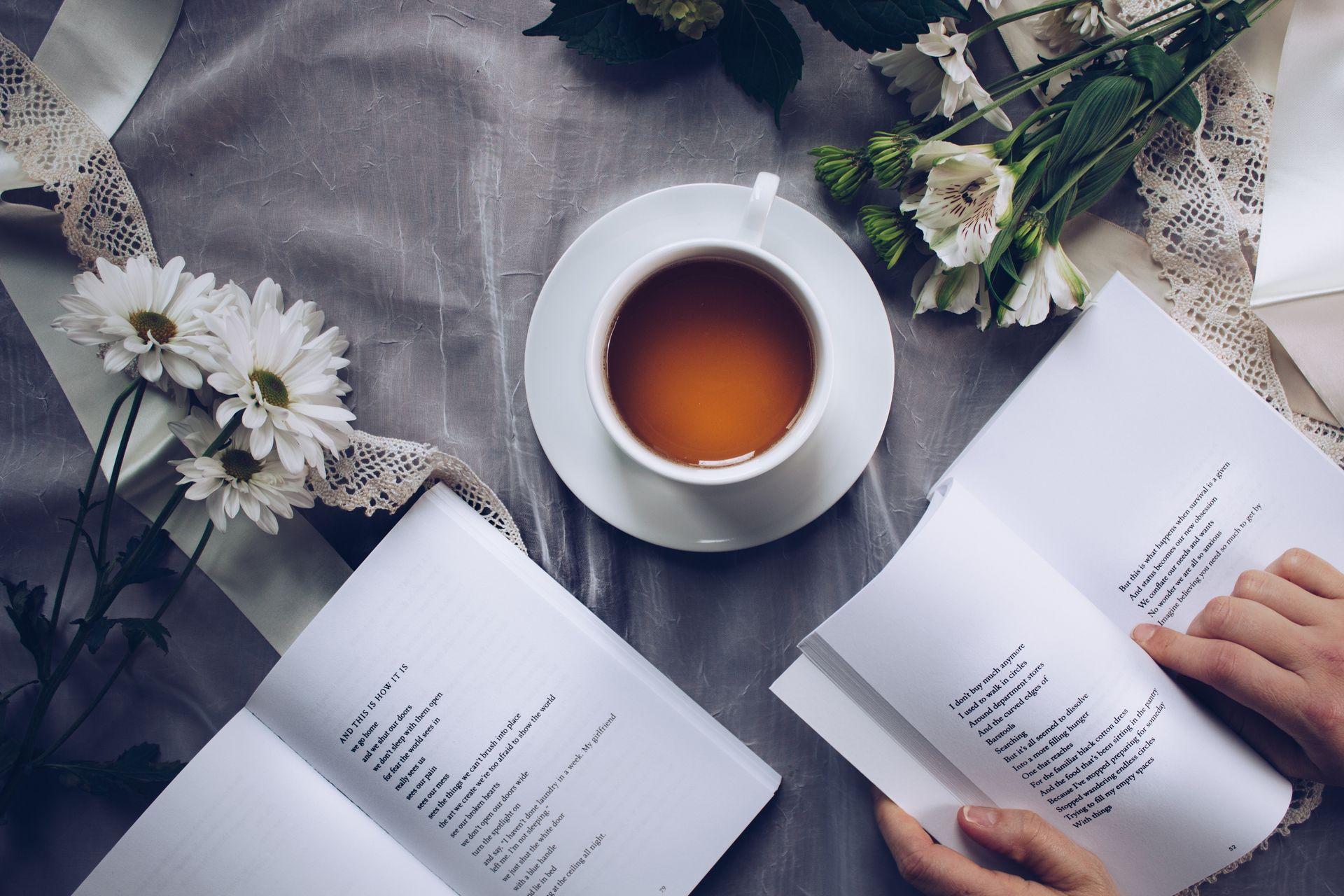 Dekorierter Tisch mit Teetasse und aufgeschlagenen Büchern