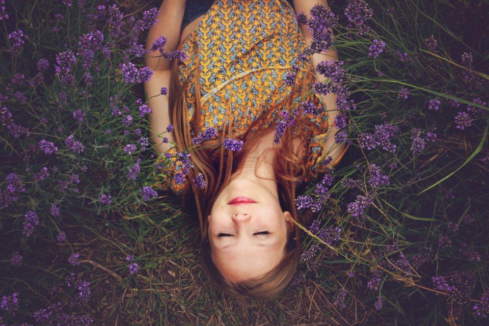 Mädchen liegt zwischen Blumen