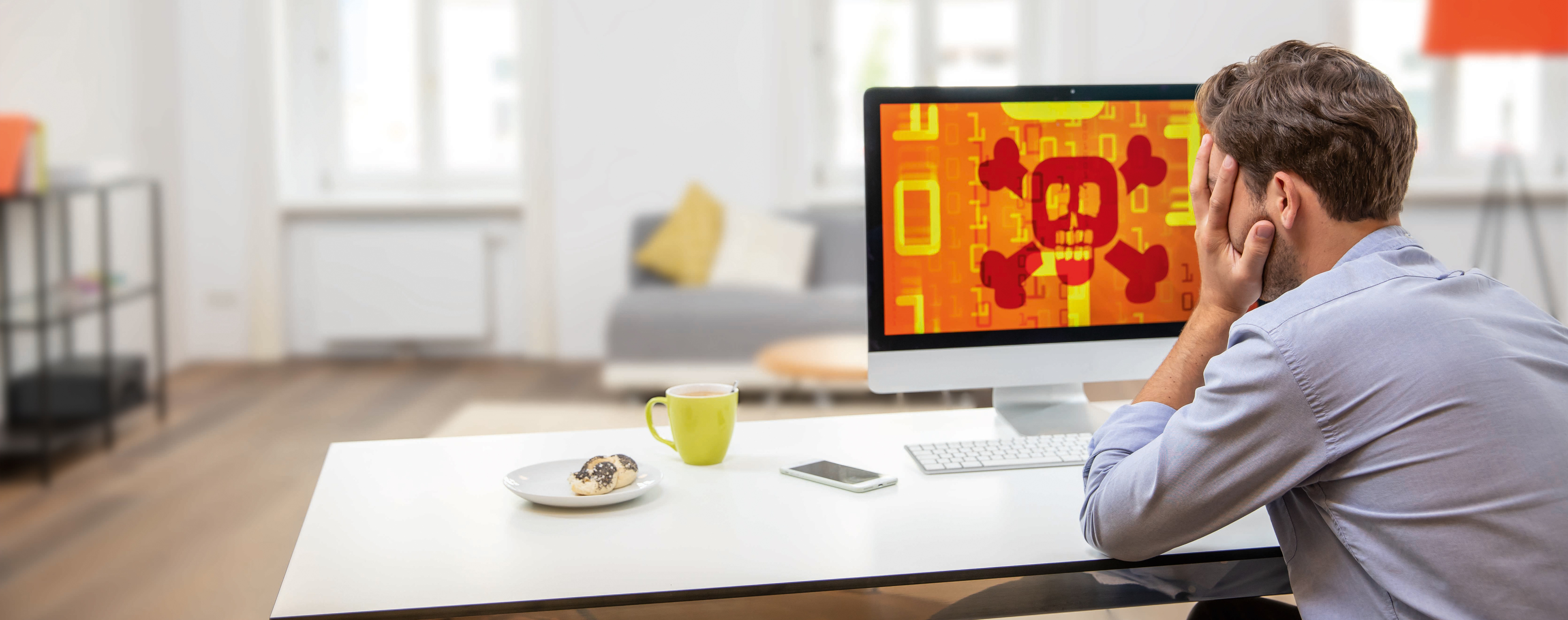 Desperate man sitting in front of a computer screen with a skull on it