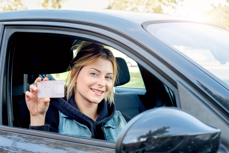 Junge Frau hält Führerschein in der Hand