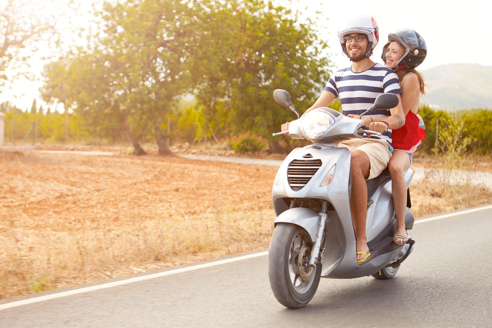 Junges Pärchen fährt mit Moped