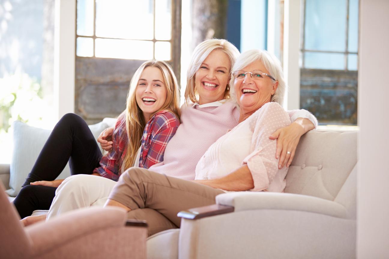 3 Frauen sitzen lachend am Sofa