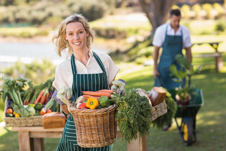 Blonde Frau mit Schürze und Gemüsekorb