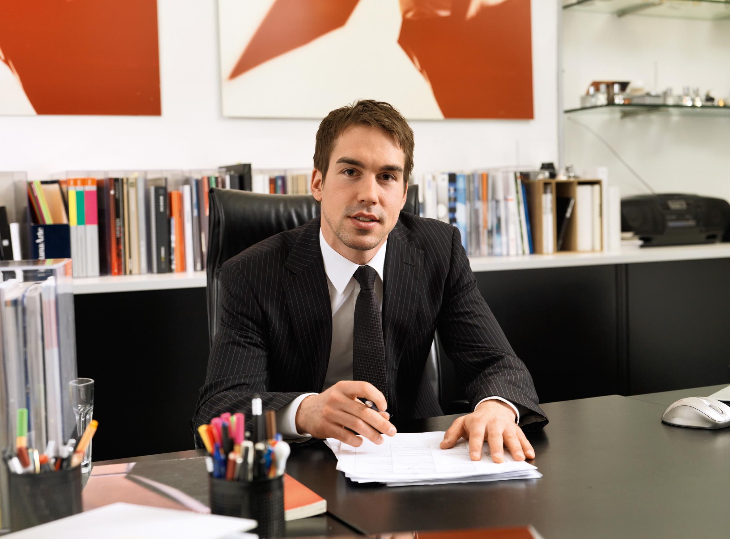 Mann in Anzug sitzt am Schreibtisch