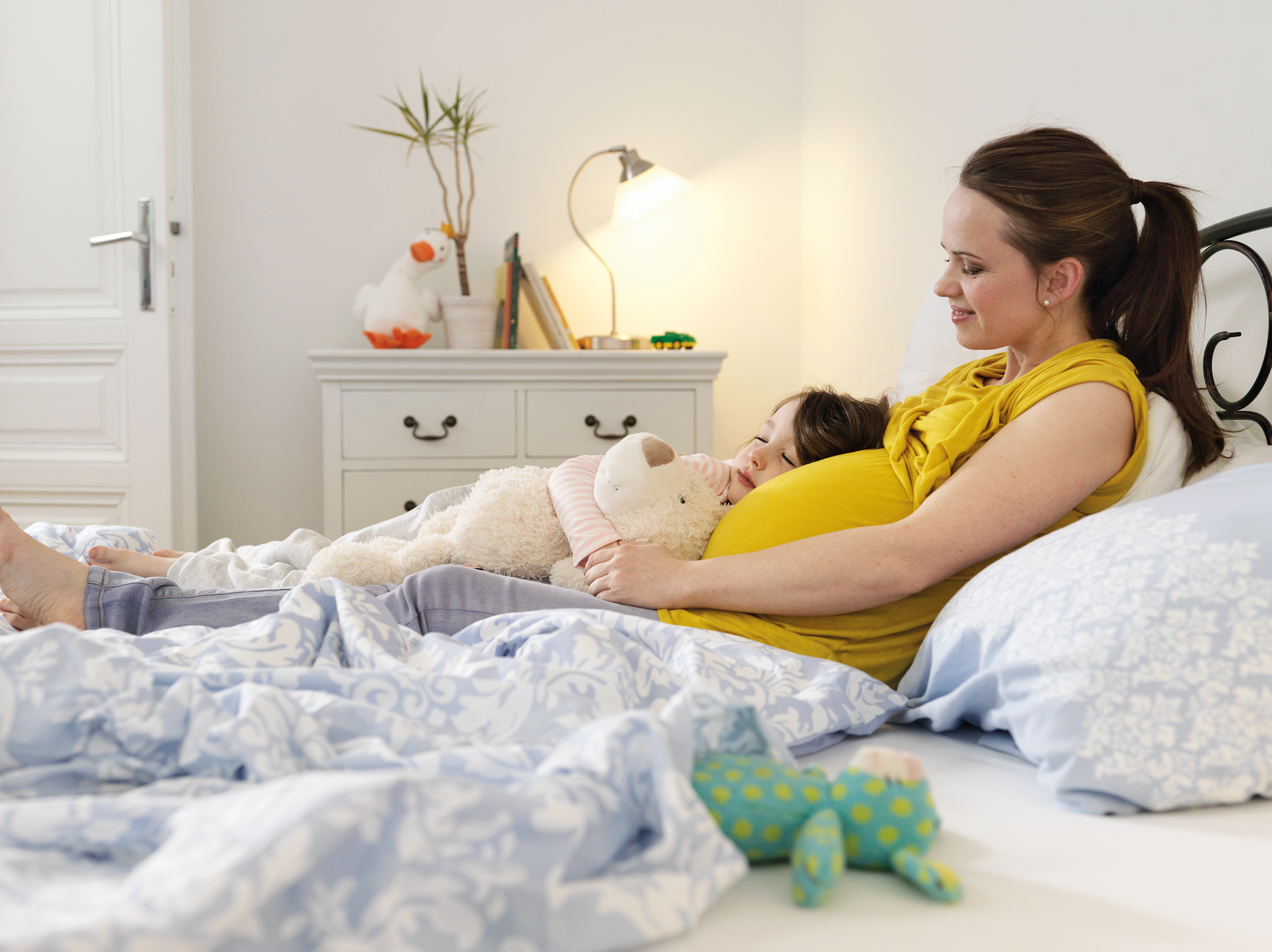 Dunkelhaarige, schwangere Frau mit Kleinkind und Kuscheltier auf einem Bett