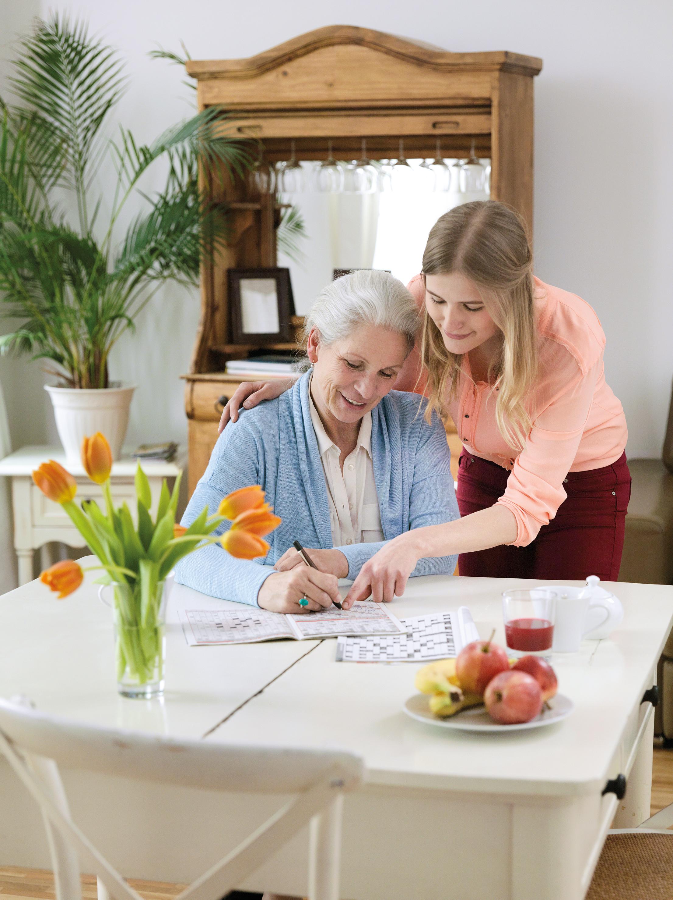 Grossmutter mit Enkelin am Tisch beim Kreuzwortraetsel