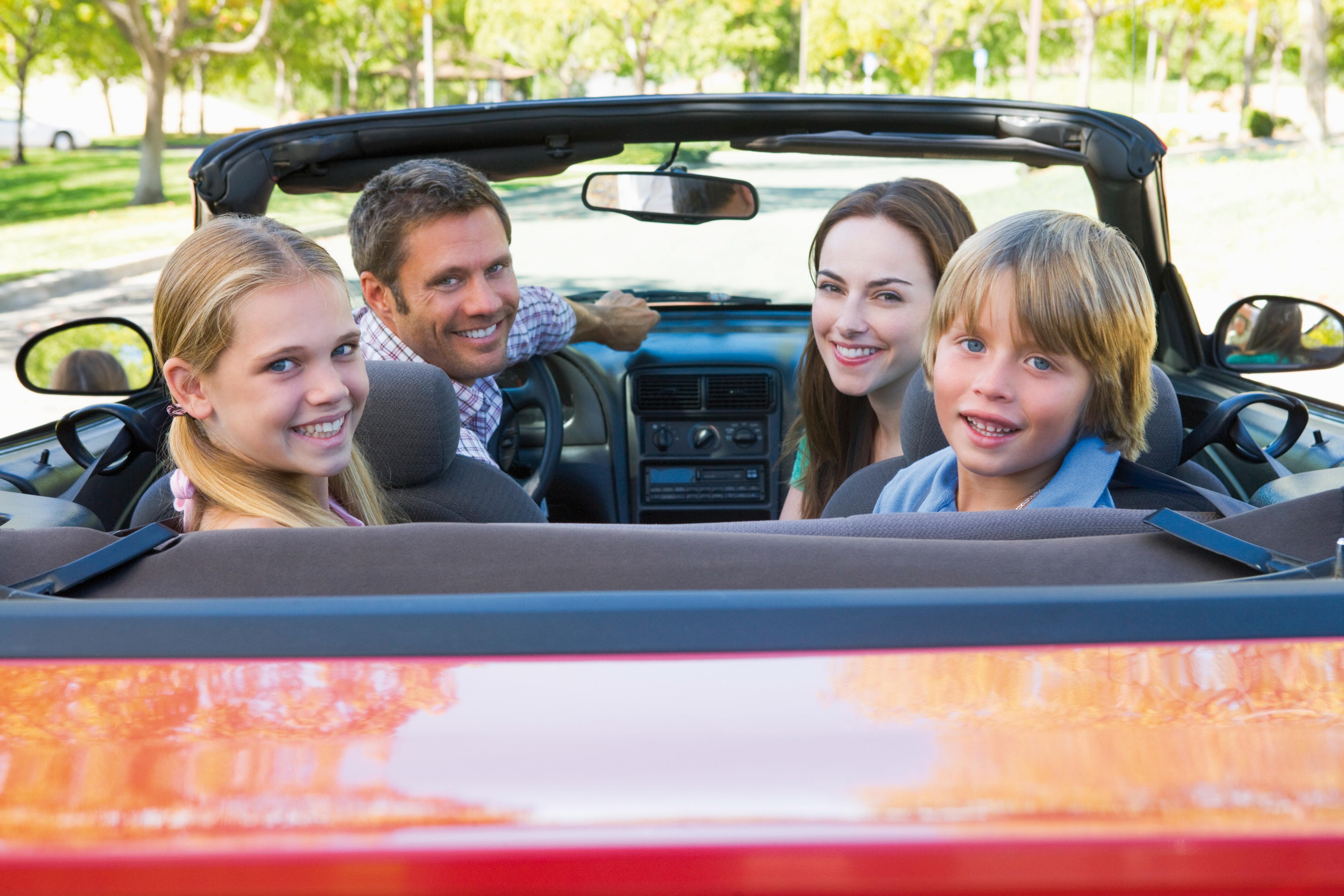 Vierkoepfige Familie in einem Cabrio