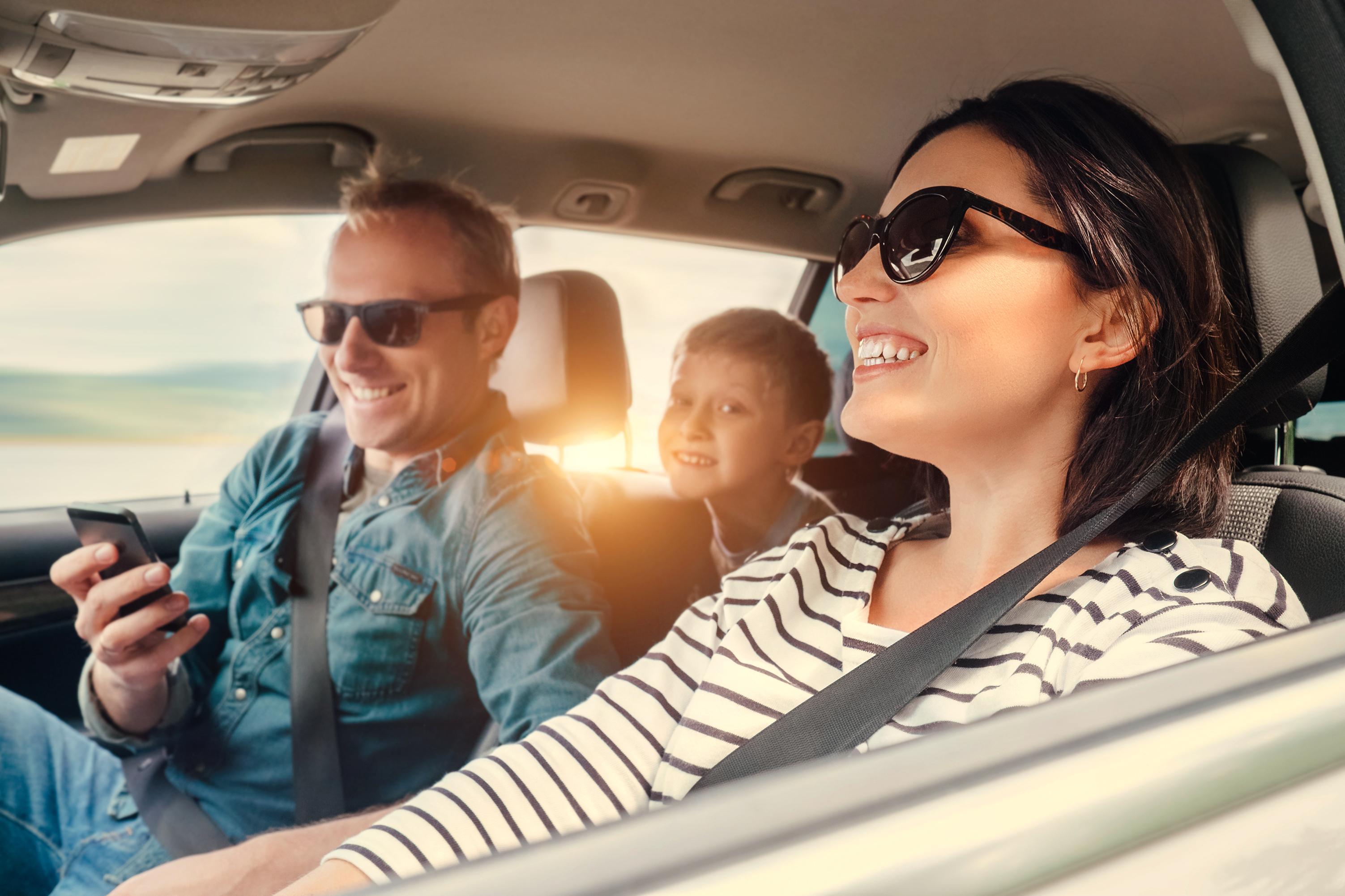 Dreikoepfige Familie im Auto