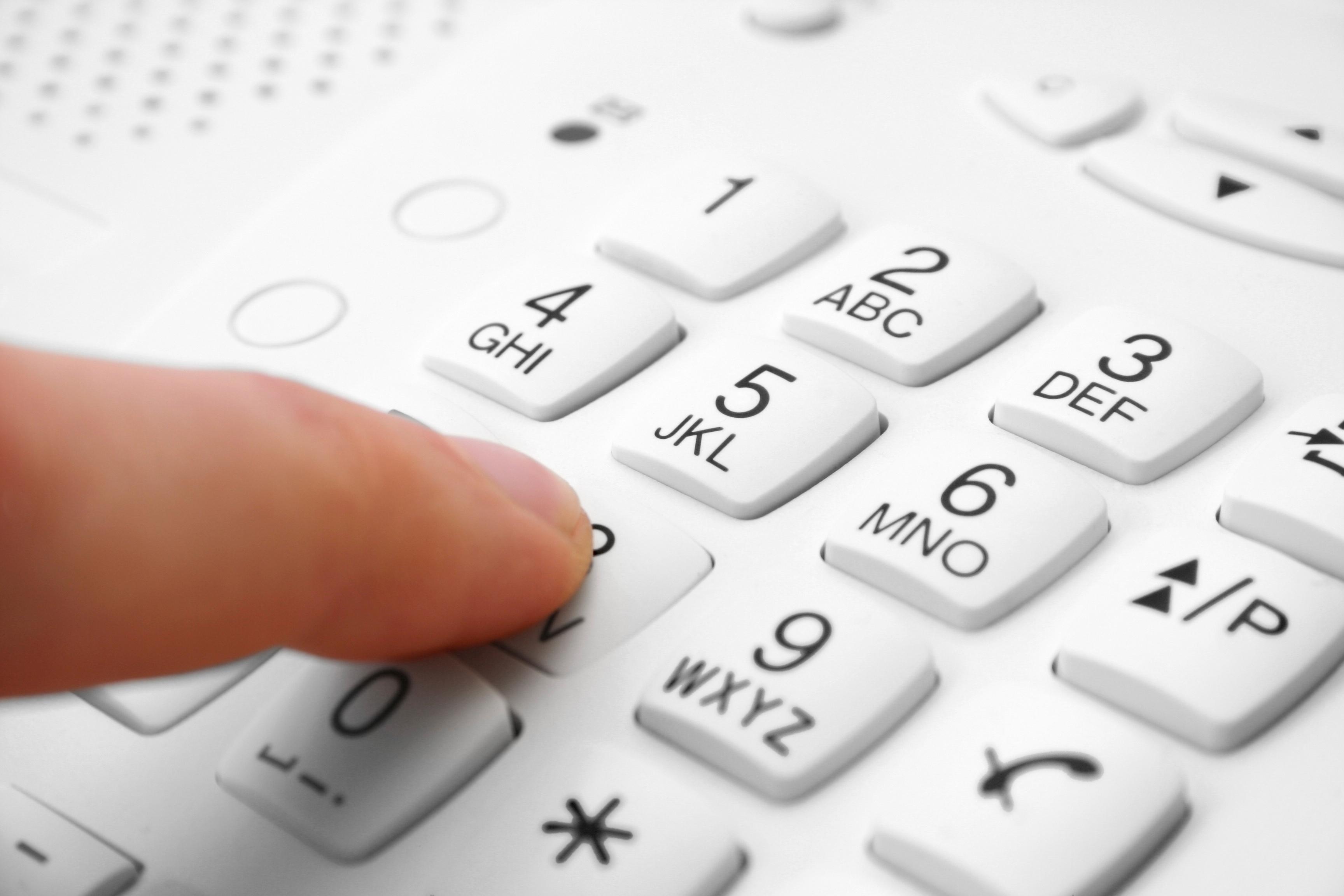 Finger auf Telefon-Tastatur