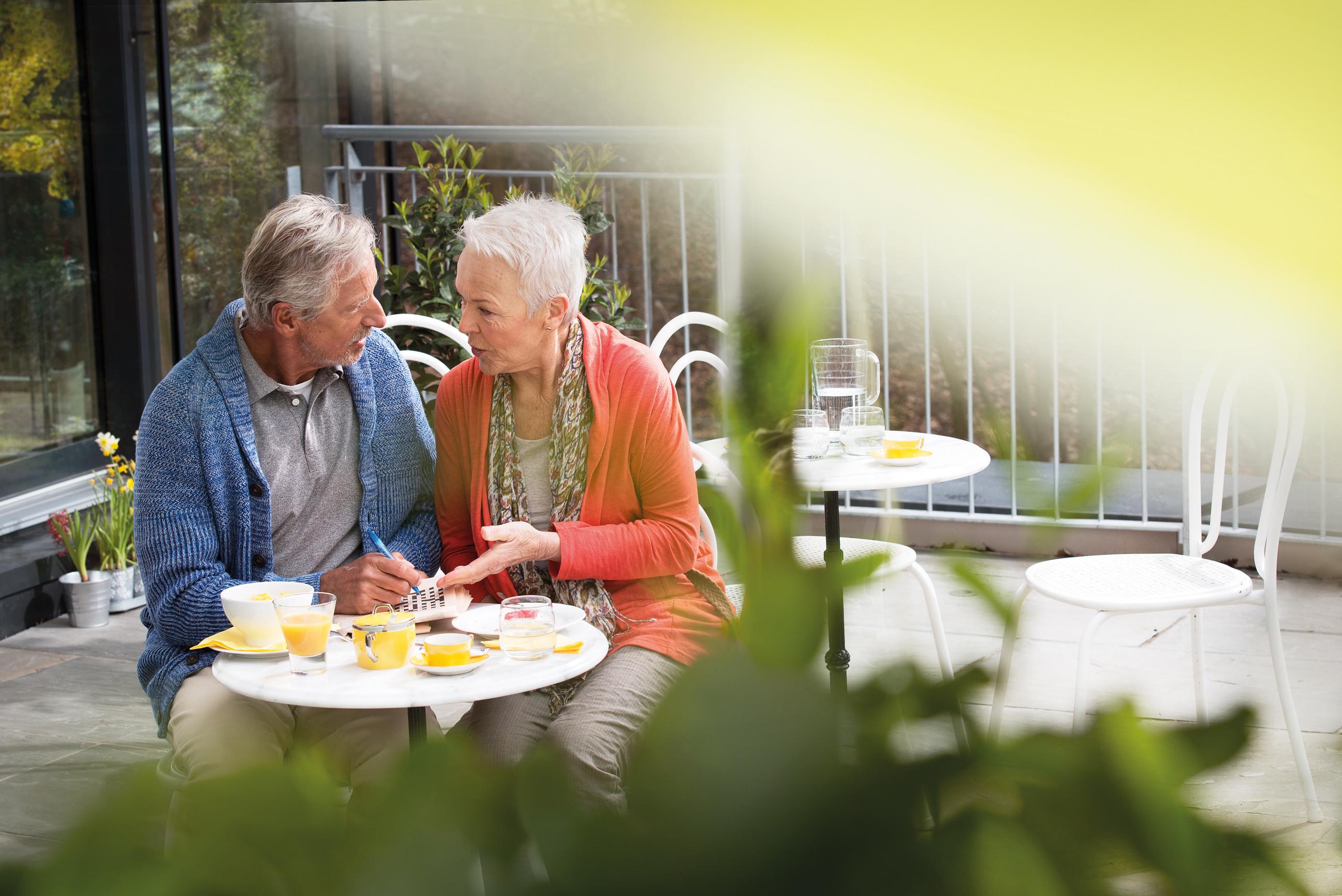 Altes Ehepaar an einem Bistro-Tisch