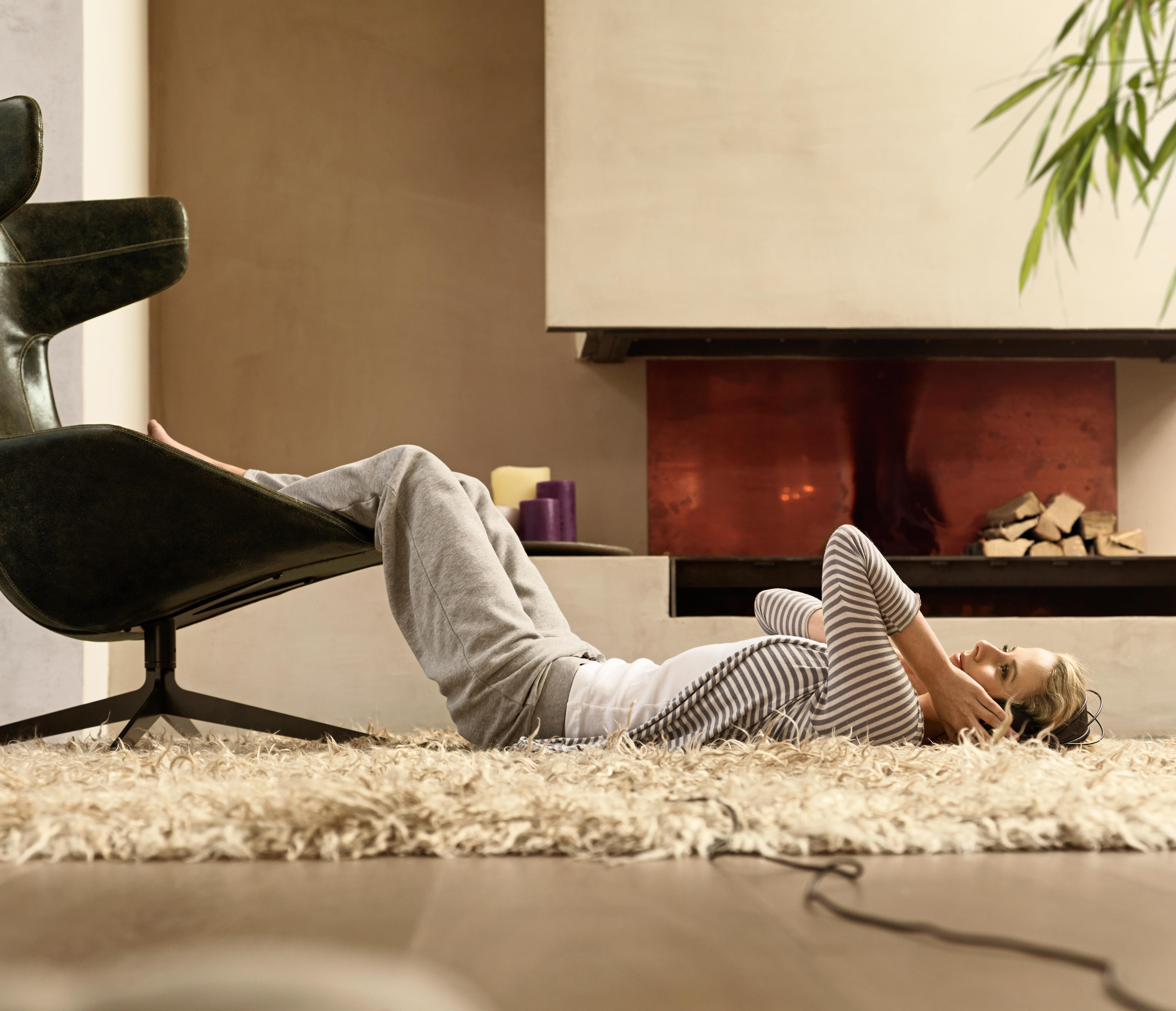 Blonde Frau auf Teppich liegend vor dem Kamin