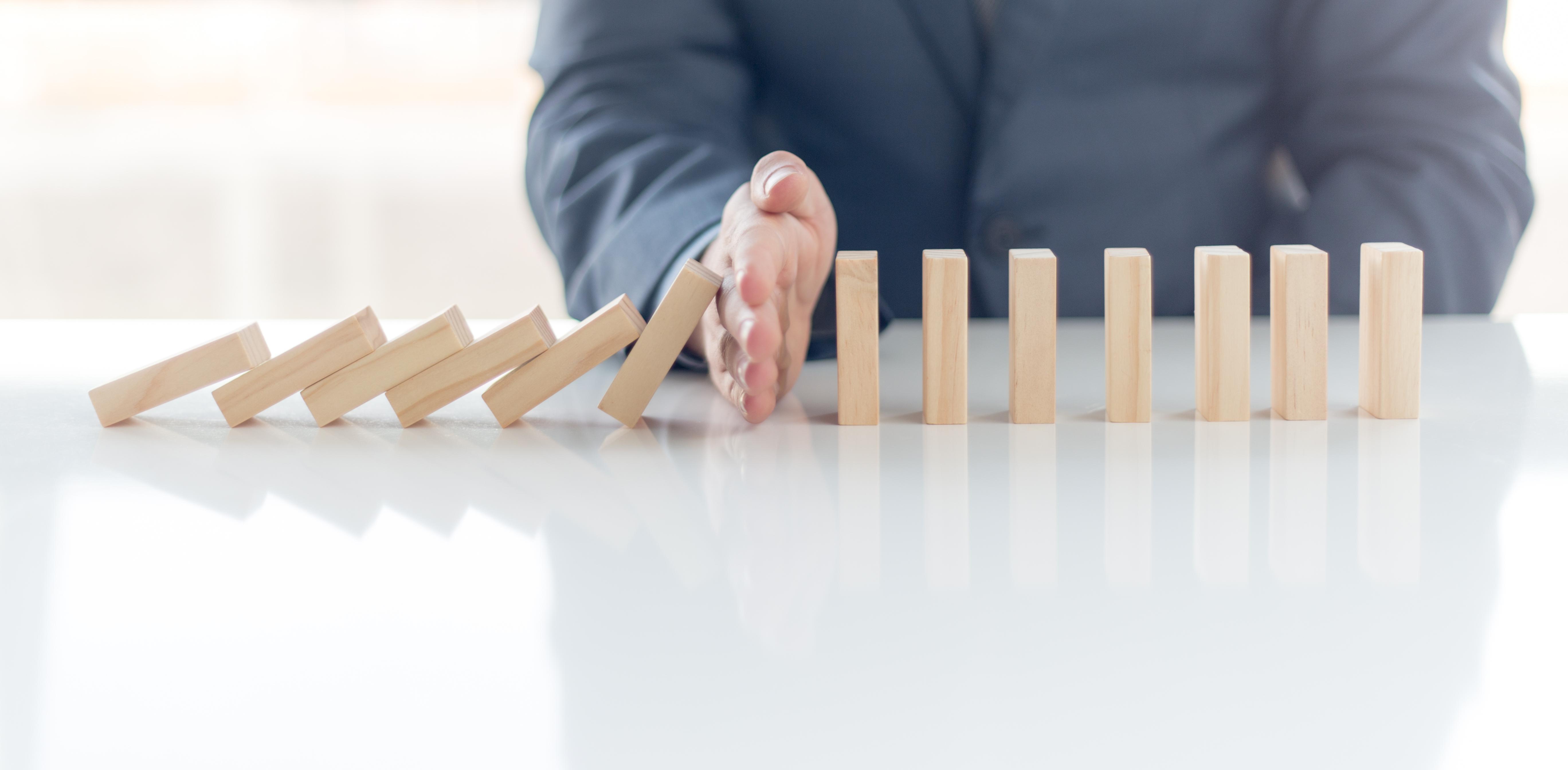 Hand, die umfallende Dominosteine aufhält