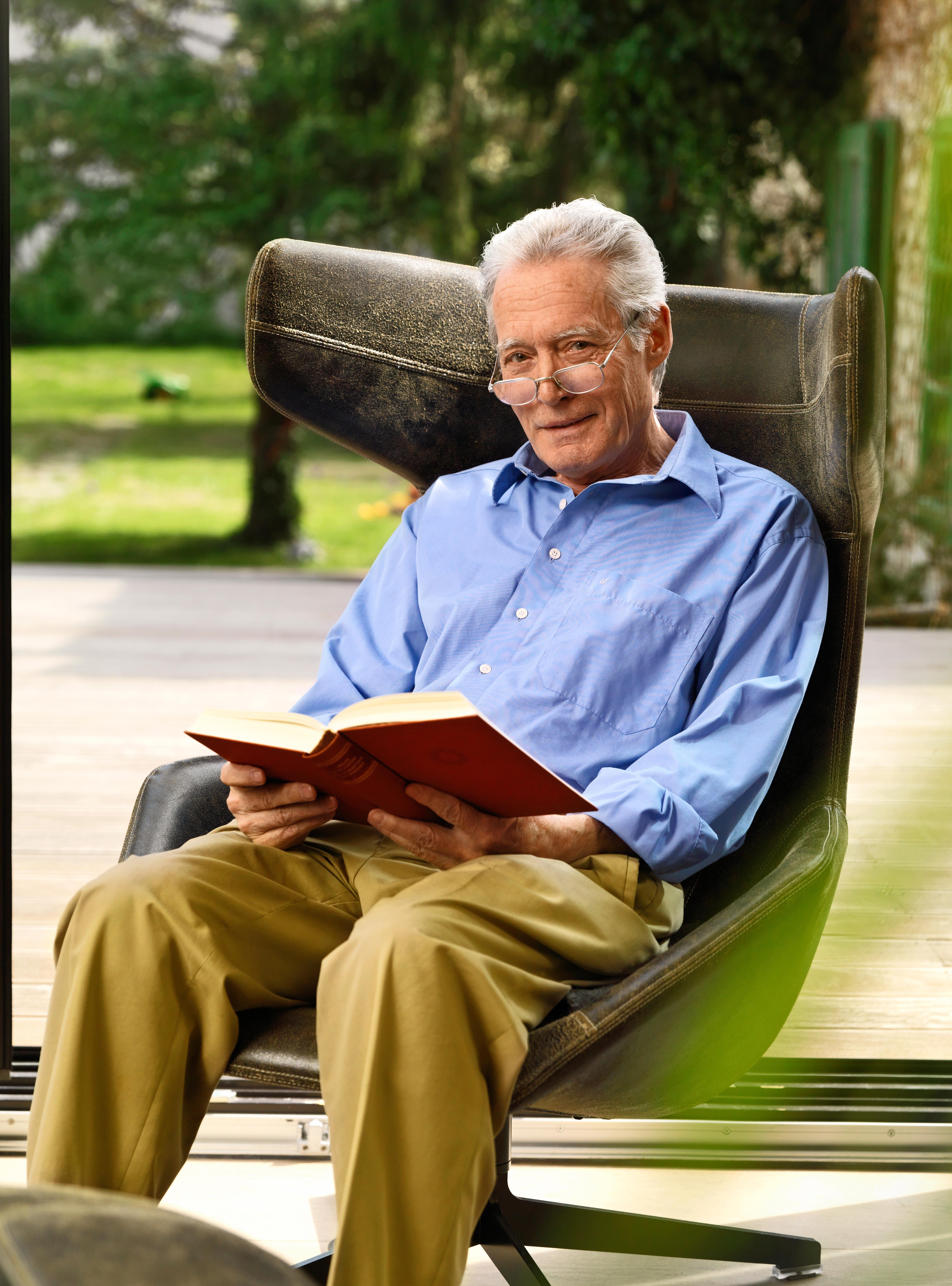 Aelterer Mann mit Brille und Buch