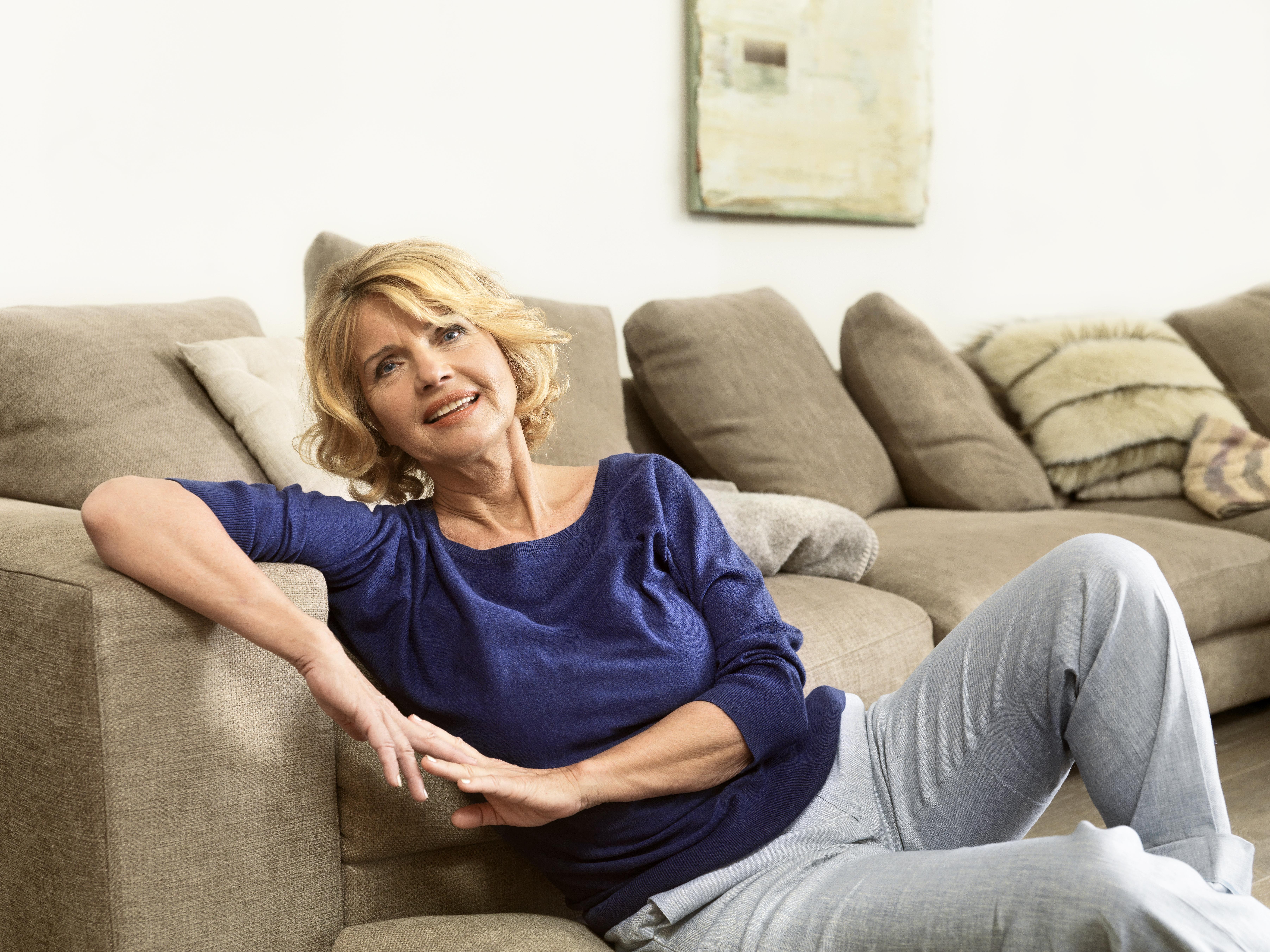 Aeltere Dame lehnt an einem Sofa