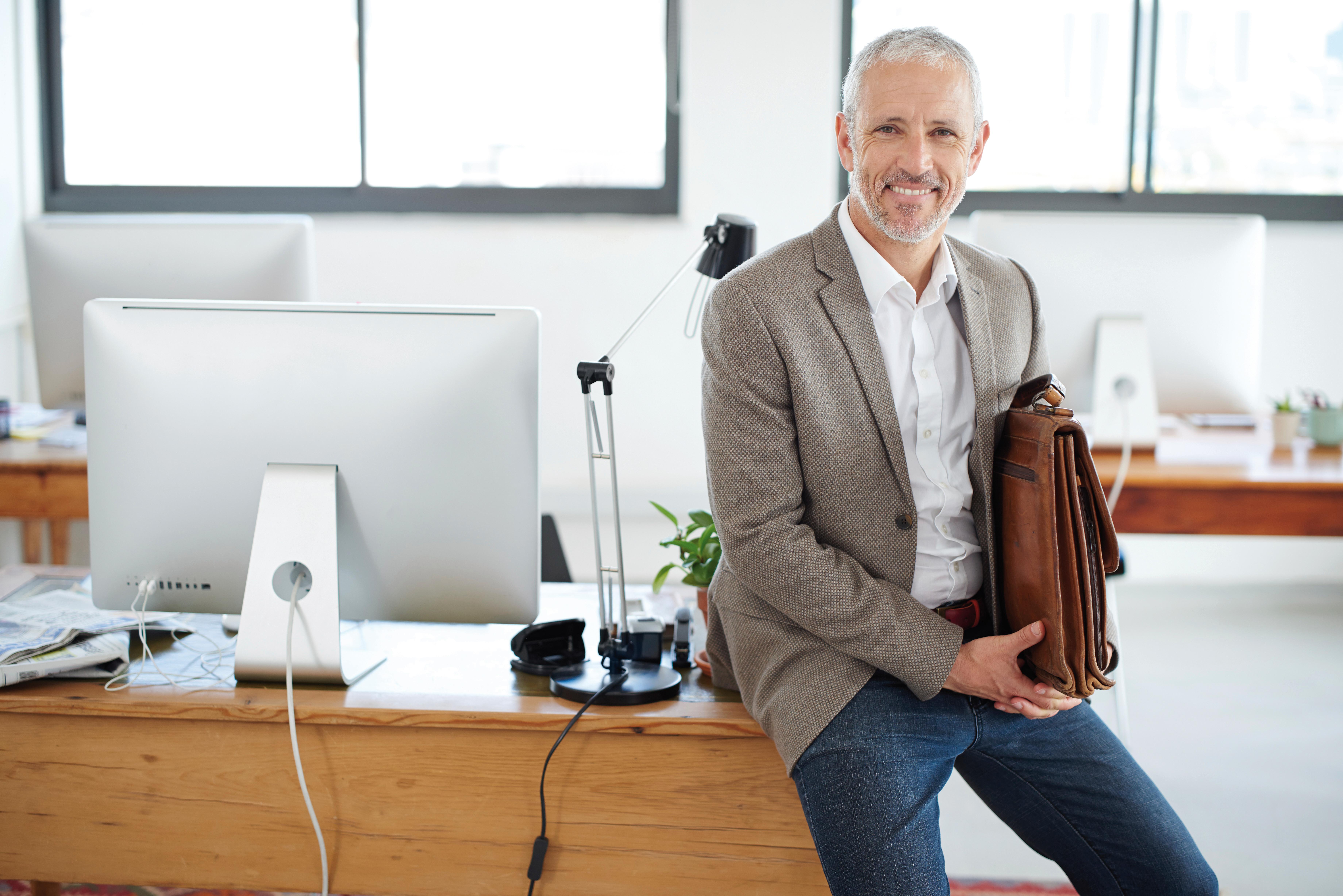 Aelterer Herr mit Aktentasche lehnt an Schreibtisch