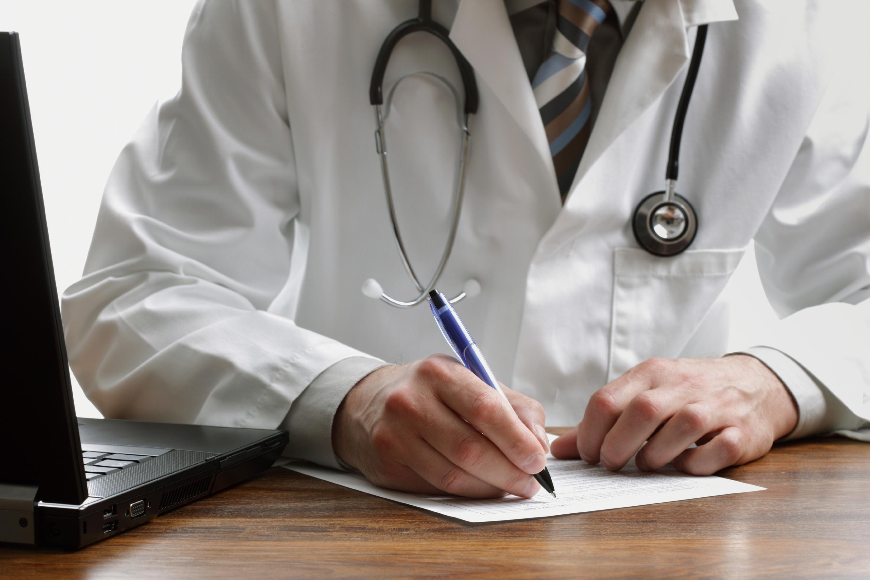 Arzt mit Stethoskop am Laptop
