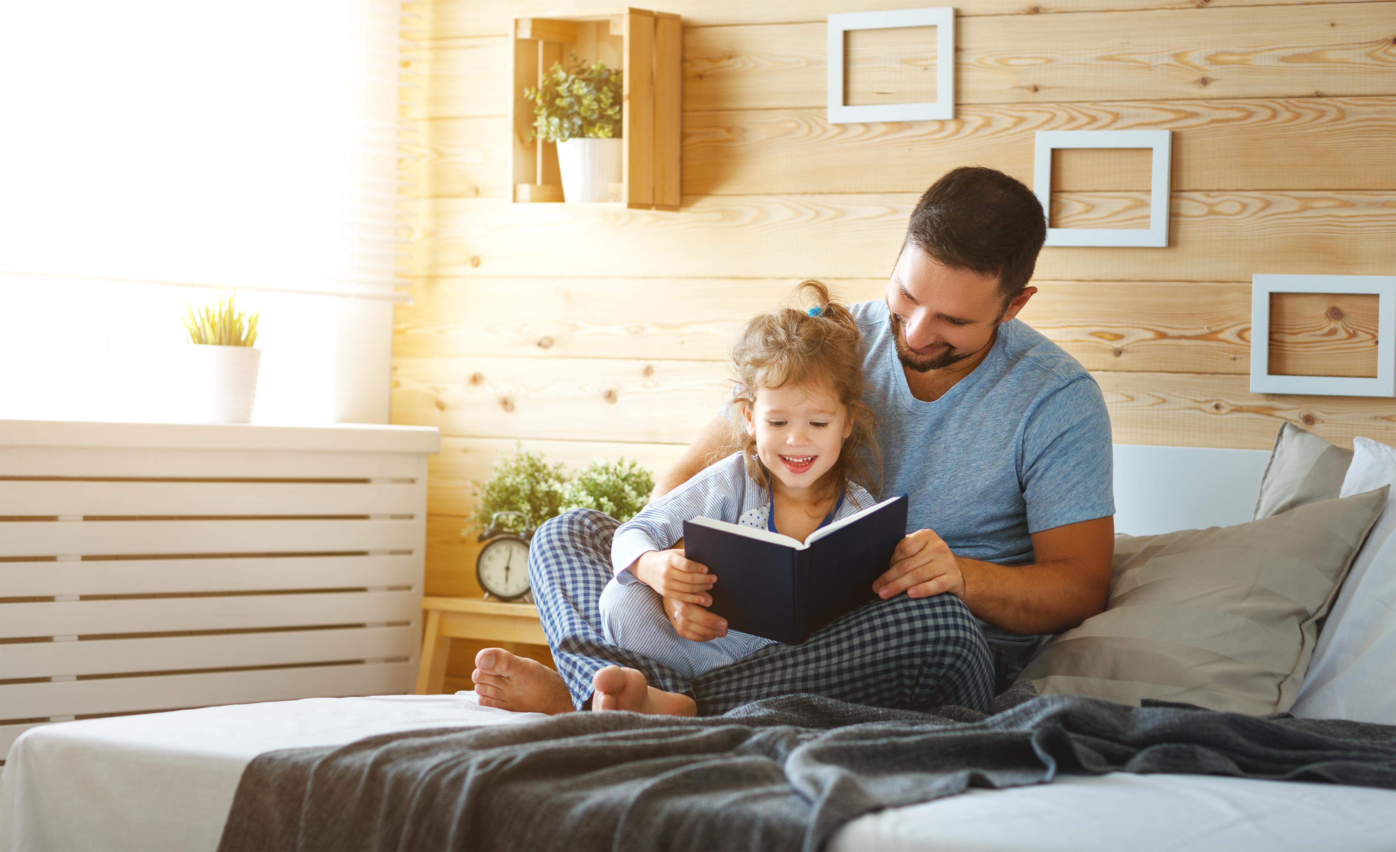 Vater liest ein Buch mit seinder Tochter