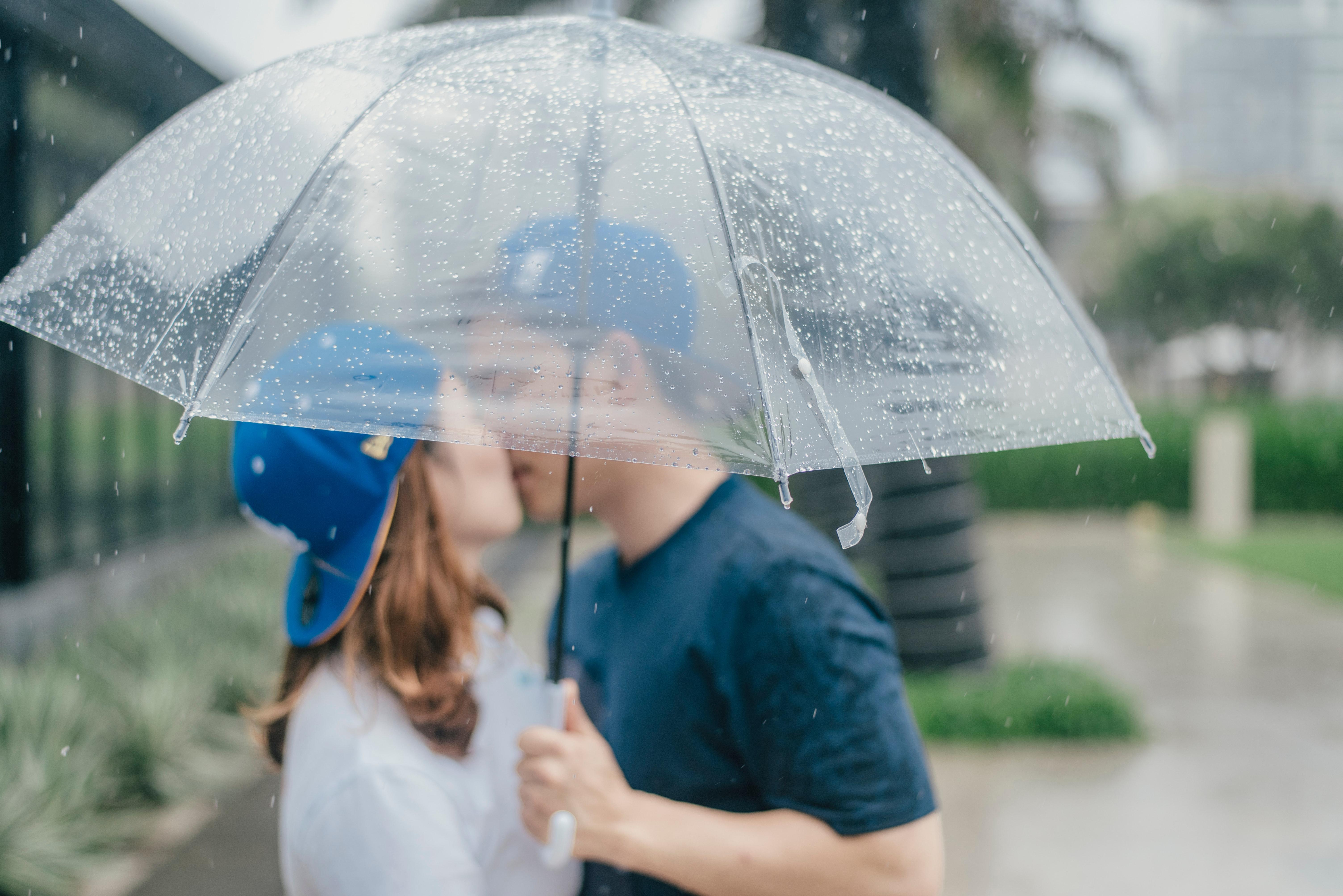 Pärchen küsst sich unter einem Regenschirm
